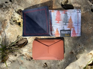 A Moft wallet and a hank pose on a rock