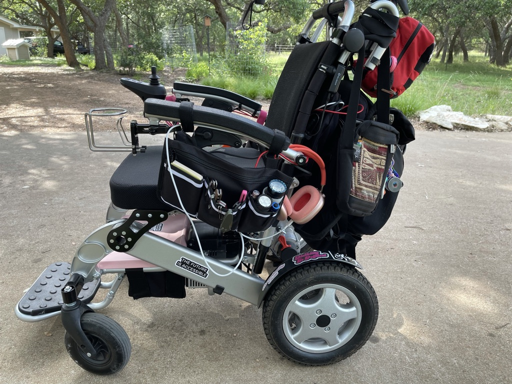 """Power wheelchair with rainbow umbrella and backpack. Sticker on frame reads, """"The Future Is Accessible""""."""