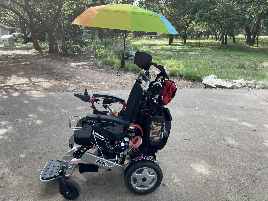 Power wheelchair with rainbow umbrella and backpack