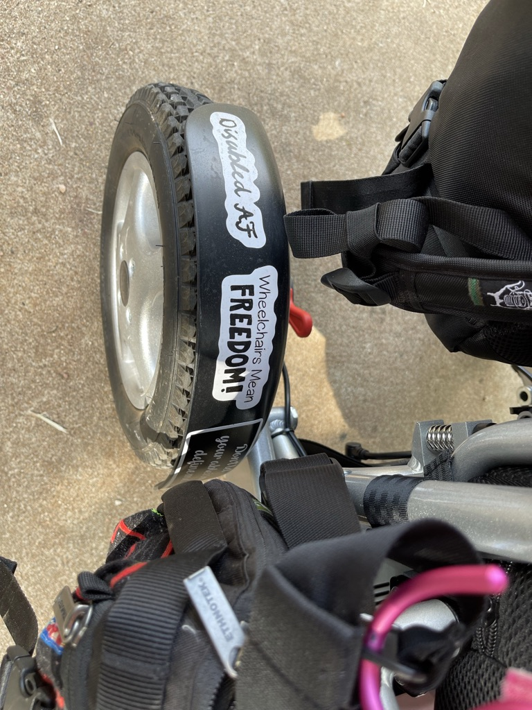 """Fender of wheelchair with """"Disabled AF"""" and """"Wheelchairs Mean Freedom"""" stickers"""